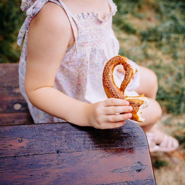 Enfant mange un bretzel au Biergarten